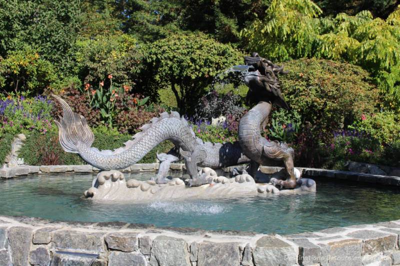Fountain with dragon sculptures amid garden plants