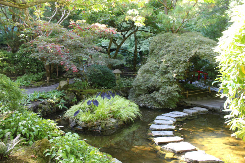 Greenery and stone walkway through water feature in Japanese Garden at The Butchart Gardens