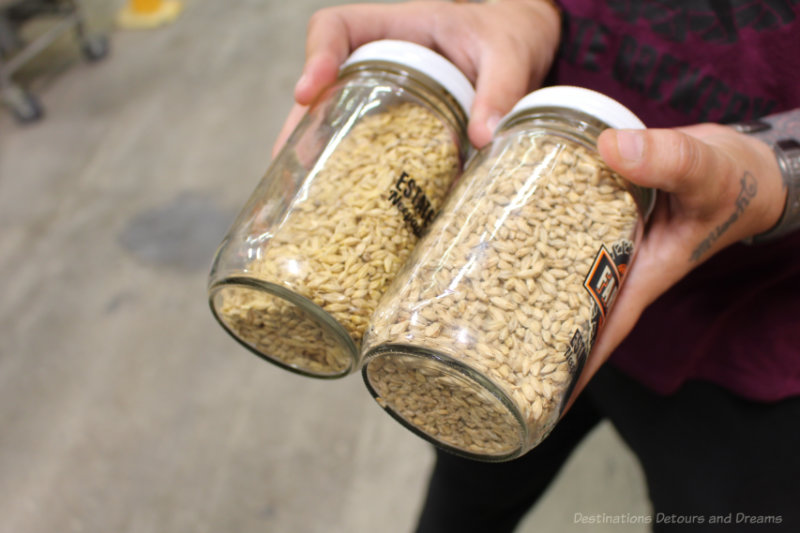 Woman holding two jars  of barley husks