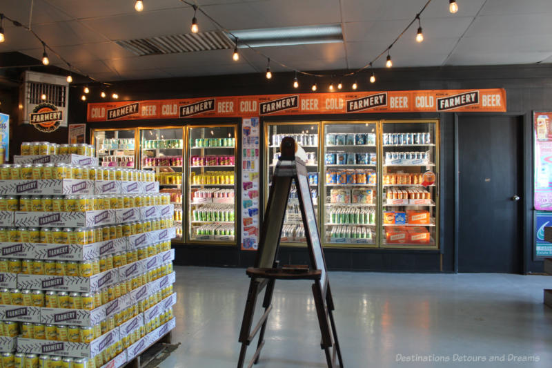 Cooler and stacks of beer and soda cans for sale
