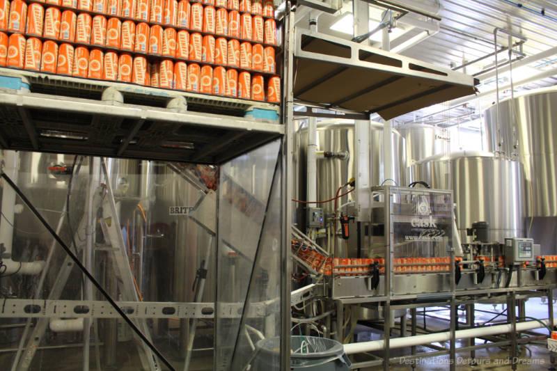 Canning machine filling orange cans of Famery beer