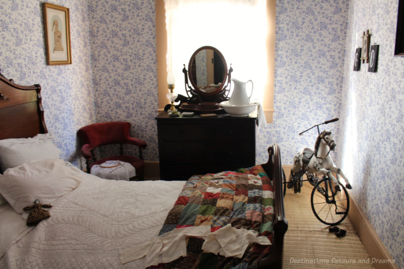 Bedroom from the late 1800s at Ross  Bay Villa with bed, blue patterned wallpaper, and a dark chest