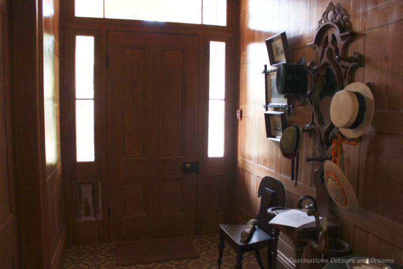 Front entryway, circa 1865, with wood-grained wallpaper, oilcloth floor, an hat rack.