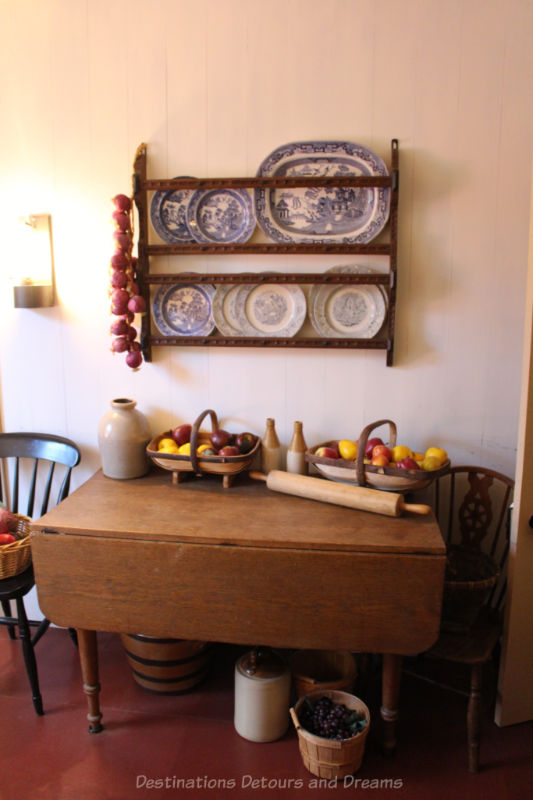 Kitchen table with baskets of fruit on it and a shelf above holding blue and white plates