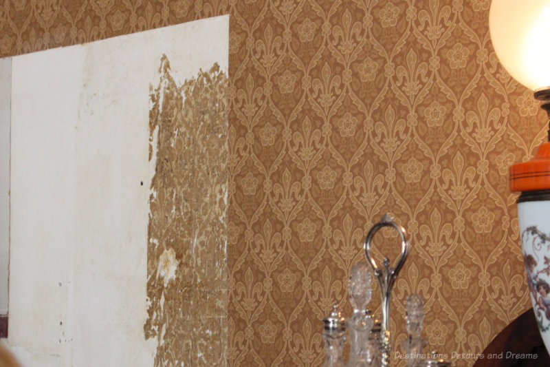 A section of wall at Ross Bay Villa with bits of the original 1800s wallpaper showing beside the recreated wallpaper on the rest of the wall