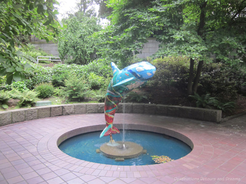 A public art piece in Vancouver features a colourfully painted orca jumping out of a fountain