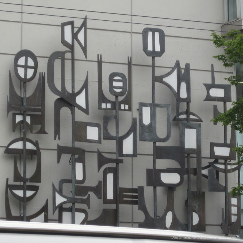 Abstract grey and white metal sculpture on wall of buidling