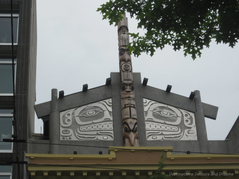 Totem pole art atop a building in Vancouver