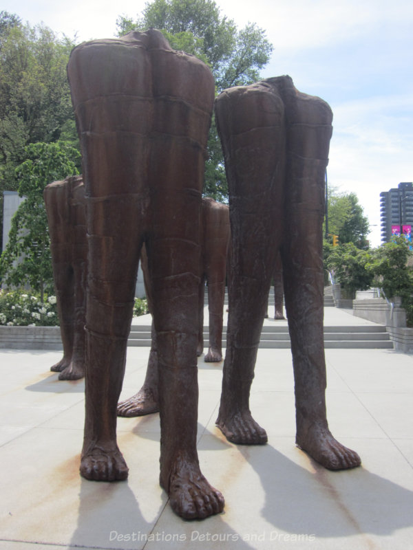 Iron statues of headless, torsless walking figures
