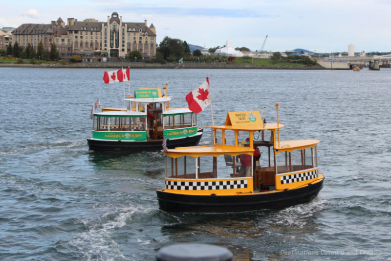 A green and a yellow Victoria Harbour Ferry boat