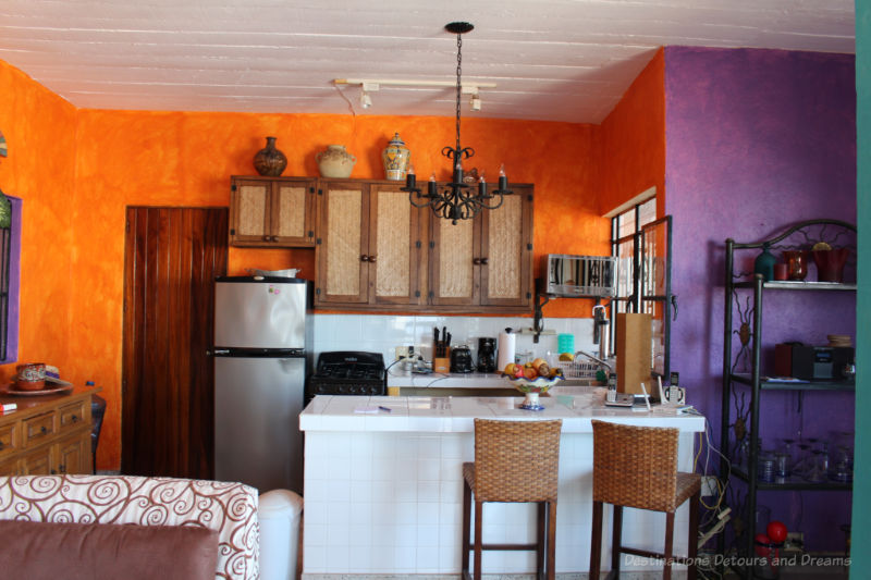Kitchen area with orange and purple walls in a Puerto Vallart Airbnb condo