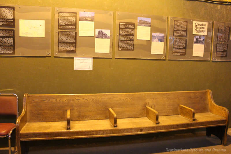 Wooden passenger waiting bench and railway history information on the wall behind it at the Winnipeg Railway Museum