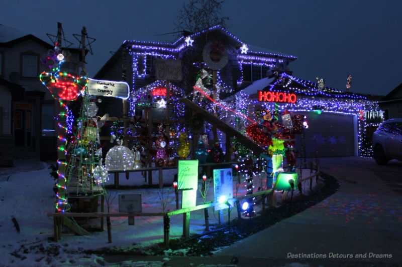 House and yard of decoration lit up with Christmas lights