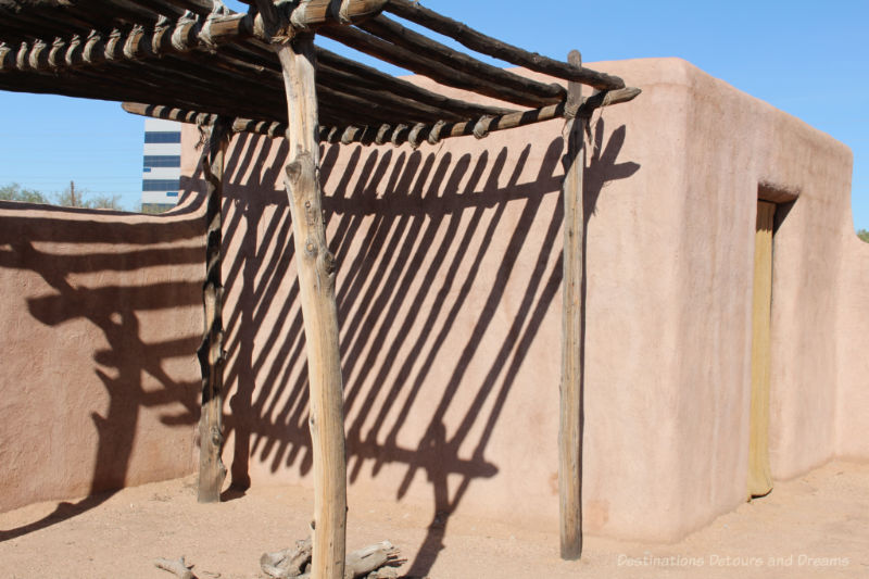 Small adobe building with a ramada shelter beside it