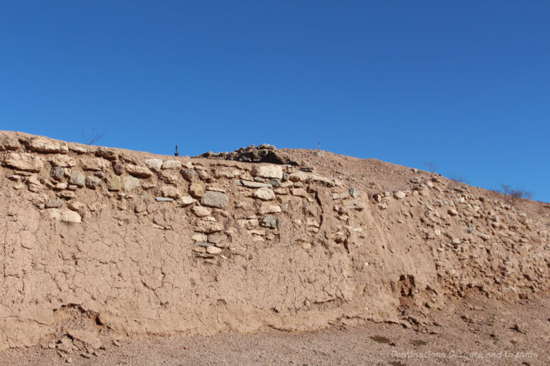 Soil and caliche wall that is the remains of an old Hohokam mound