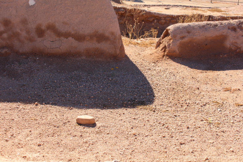 Sandy wall ruins and a shadow along the soil - remains of a Hohokam solstice room