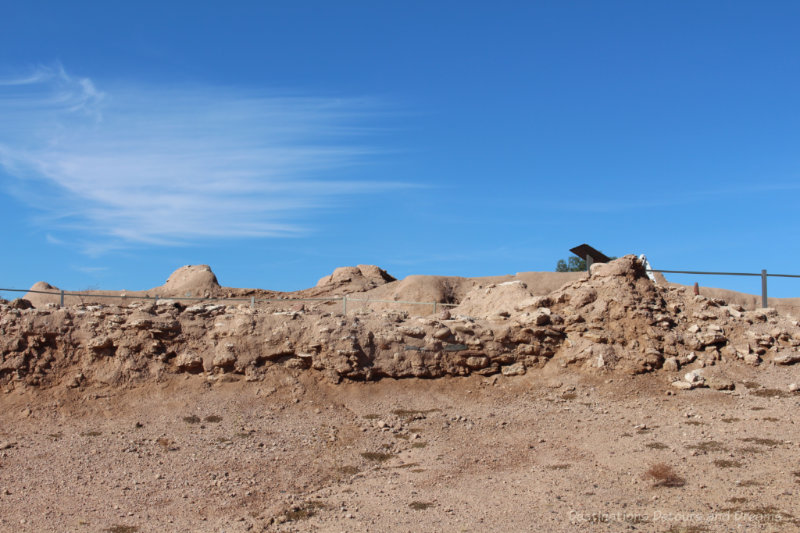 Sandy coloured mounds - Hohokam ruins - against a blue sky