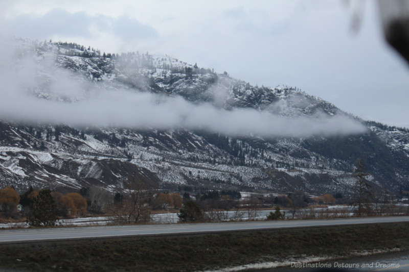 A line of clouds in the middle of partially snow-covered mountains on a winter day