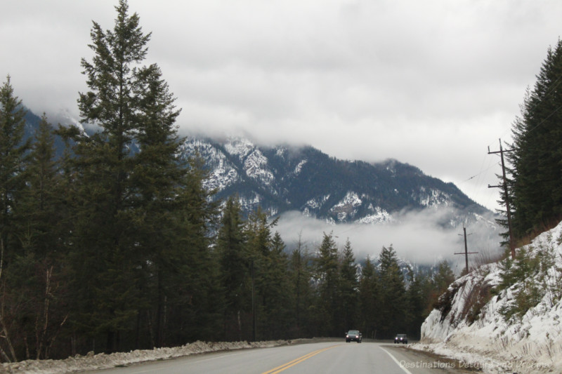 Highway lined with fir trees amid snow-covered mountains with low-lying clouds on a winter drive through British Columbia