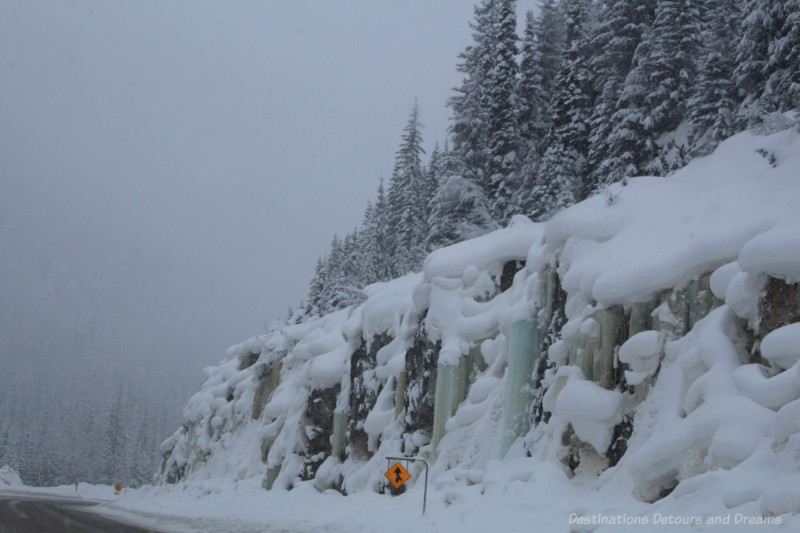 British Columbia mountain with snow-covered fir trees atop a rock side covered with snow and frozen waterfalls