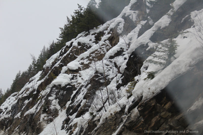 Snow partially covering rock slope of British Columbia mountain