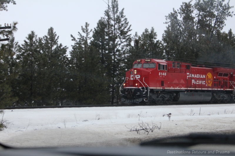 Canadian Pacific train engine driving past fir tress in British Columbia mountains