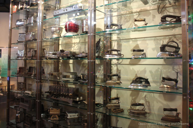 A display on many shelves in a glass case of small electrical appliances over the years