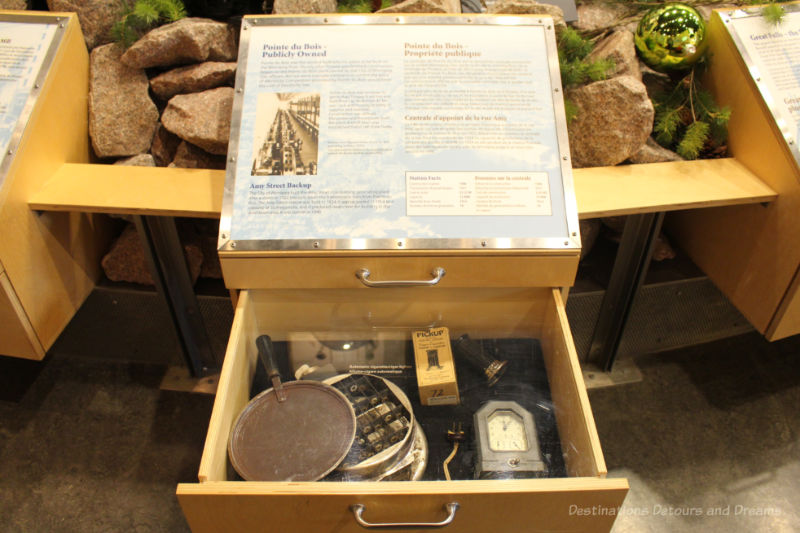 Open drawer under museum display showing electrical artifacts and electrical history information