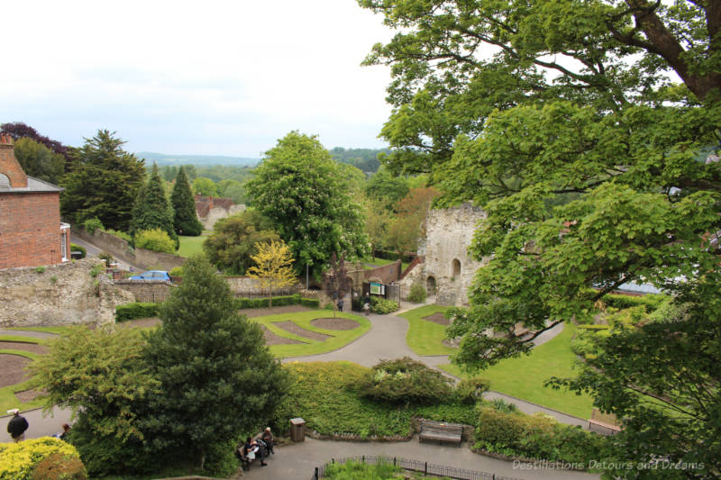 Looking down over green space, walkways, tress and the stone entrance wall to Guildford Castle