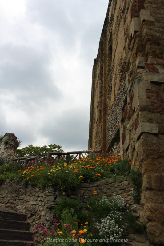 Yellow and orange flowers blooming alongside old stone walls of a medieval castle tower in Guildford