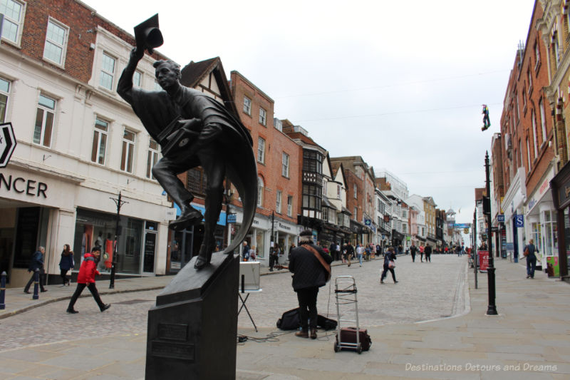 Cobblestoned pedestrian high street of Guildford with statue of the Surrey Scholar in the foreground