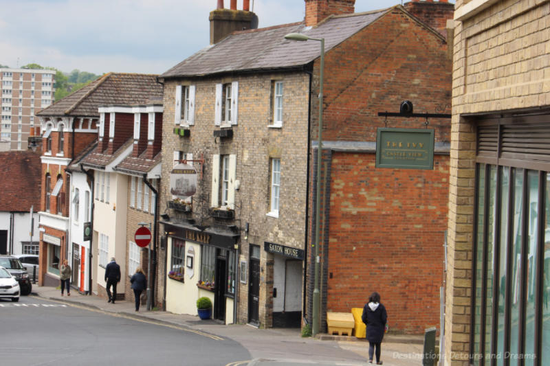 Street on a a hile with stone buildings on the left including The Keep pub