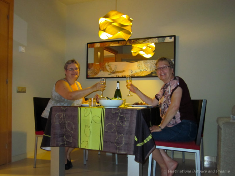 Two women having dinner and raising a glass of wine in their home exchange apartment
