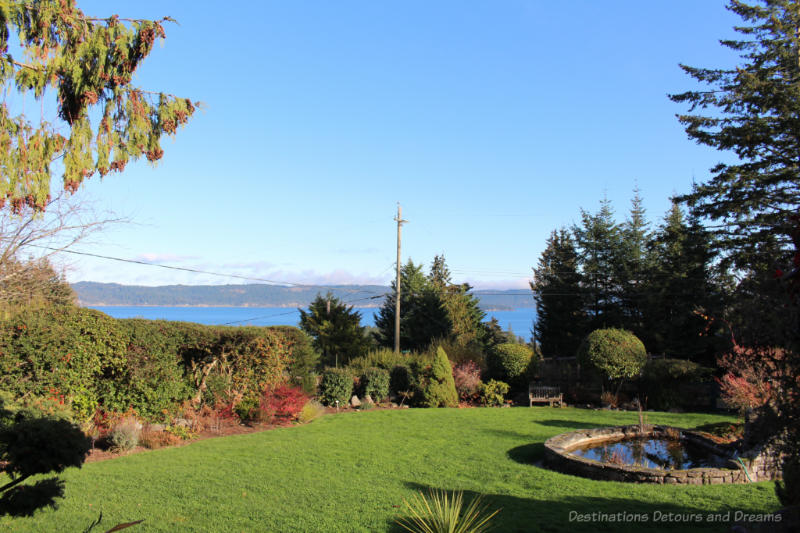 View of landscaped yard l on Salt Spring Island looking out over water with mountains beyond