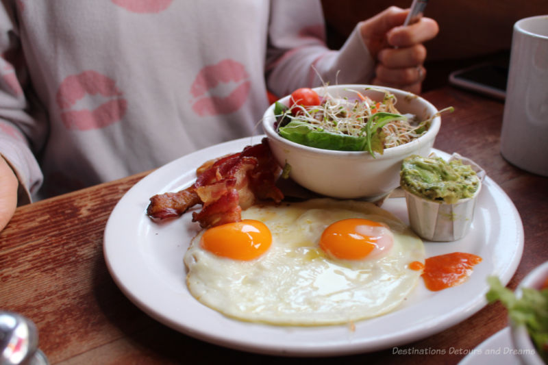 Brunch dish of eggs, bacon, greens, and guacamole