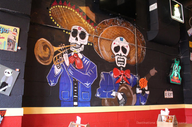 Painting on wall of El Loco Taco features musicians with blue suits, skull heads, and large sombreros