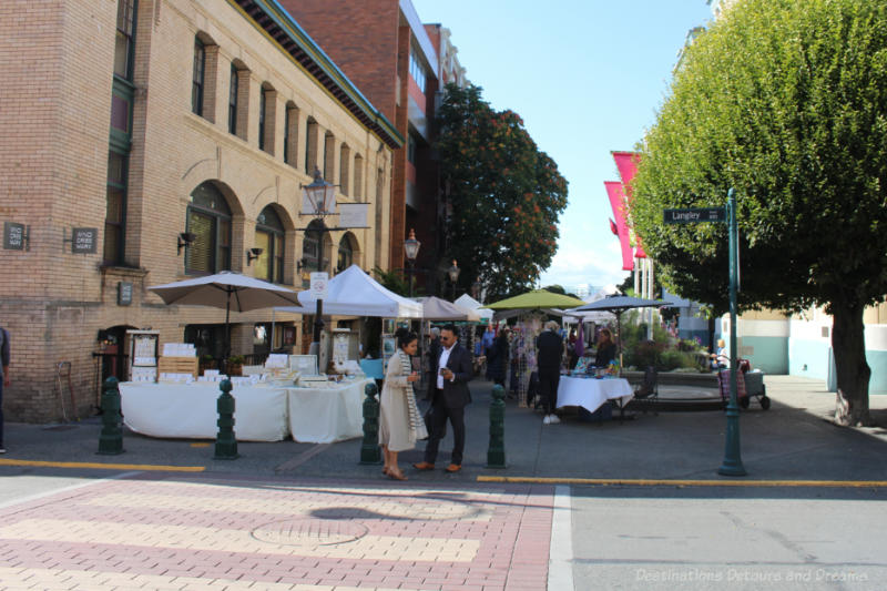 Outdoor vendors in a wide alley in downtown Victoria