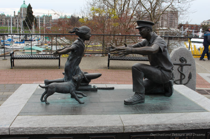 Bronze statue of a little girl and her dog running toward the open arms of her kneeling father in a sailor's uniform