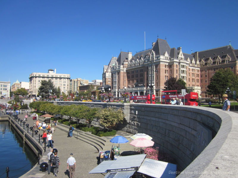Pedestrian walkway in the lower causeway of Victoria Inner Harbour with the iconic Empress Hotel in the background