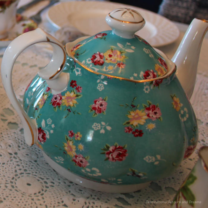 China tea pot with turquoise body decorated with yellow, white, and rose flowers and white handle and spout