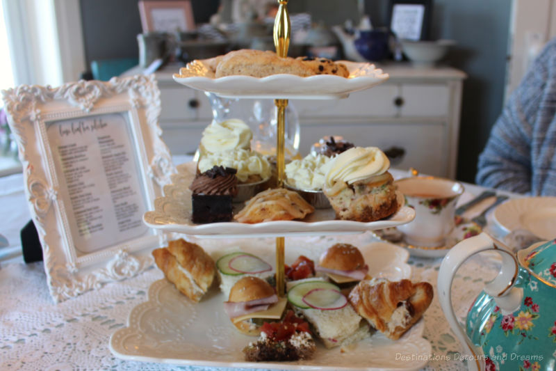 Three-tiered tray of finger sandwiches, sweets, and scones for afternoon tea at The Ol Farmhouse Cafe in Rosenort, Manitoba
