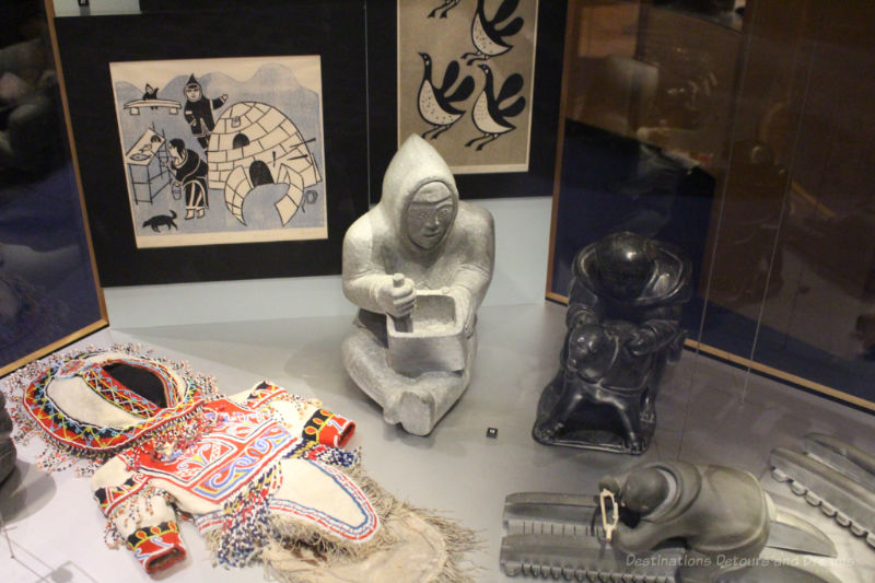 A collection of Inuit art pieces - paintings, beaded outfit, and stone carvings