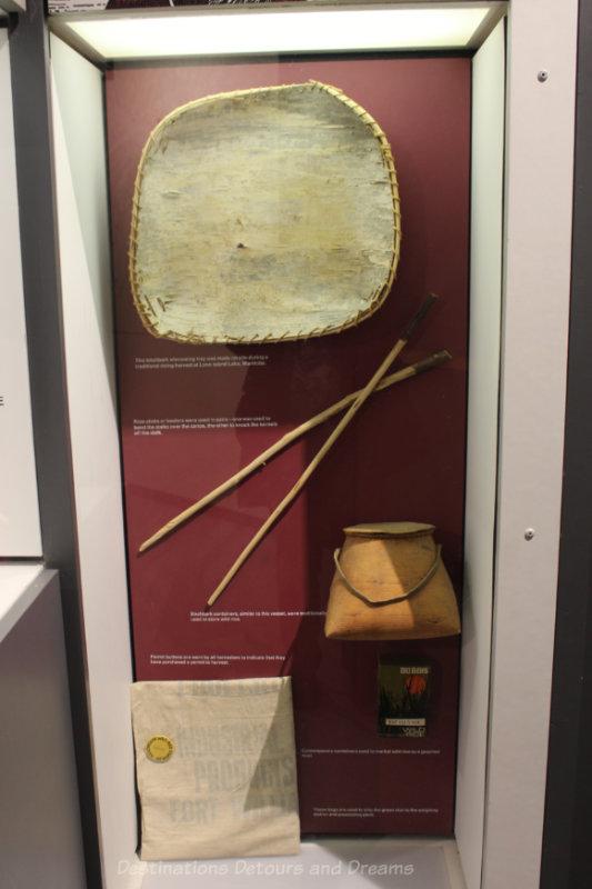 Display of tradition wild rice harvesting equipment - birchbark winnowing tray, rice-sticks, and birchbark containers
