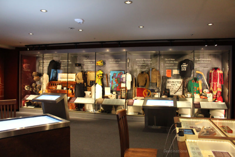 Long wall contain display cases of different themes in the Winnipeg Gallery at Manitoba Museum