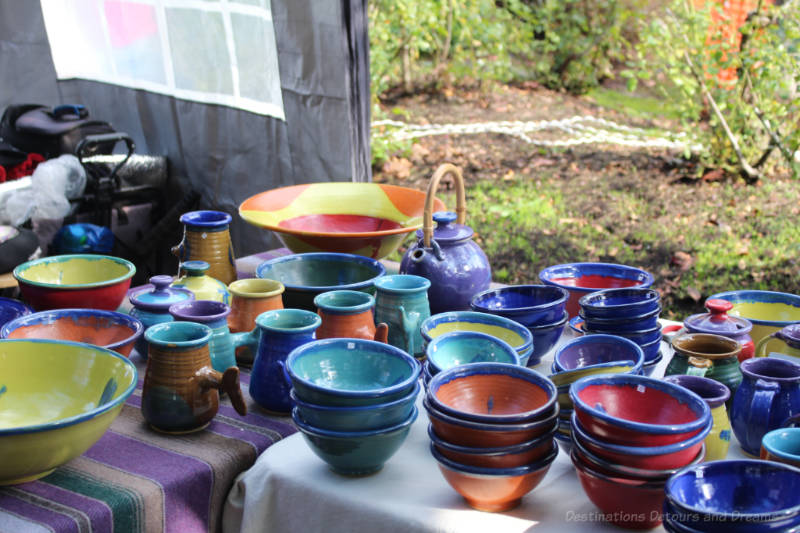 Table containing bright blue, red, and yellow pottery at Salt Spring Island Saturday Market
