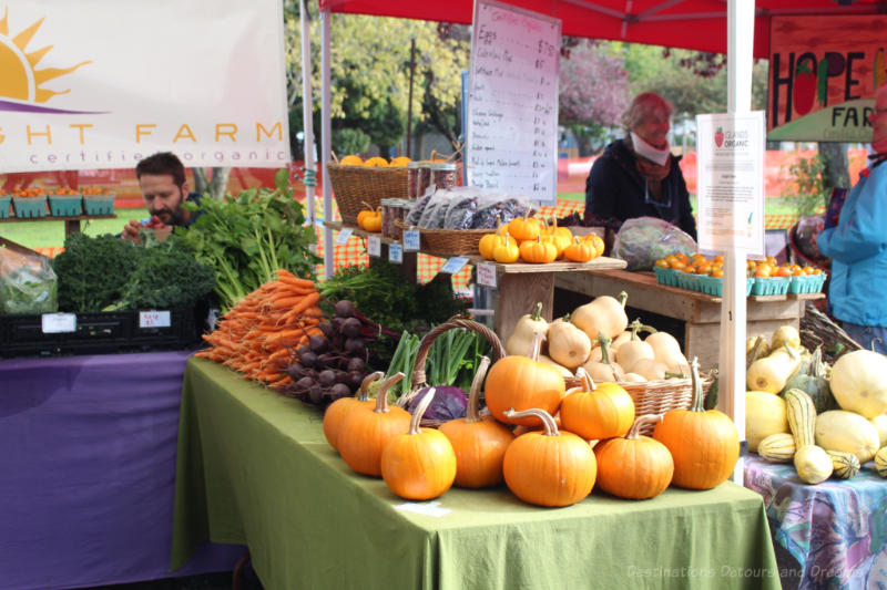 Vegetable stand containing pumpkin, squash carrots, and beets at Salt Spring Island Saturday Market
