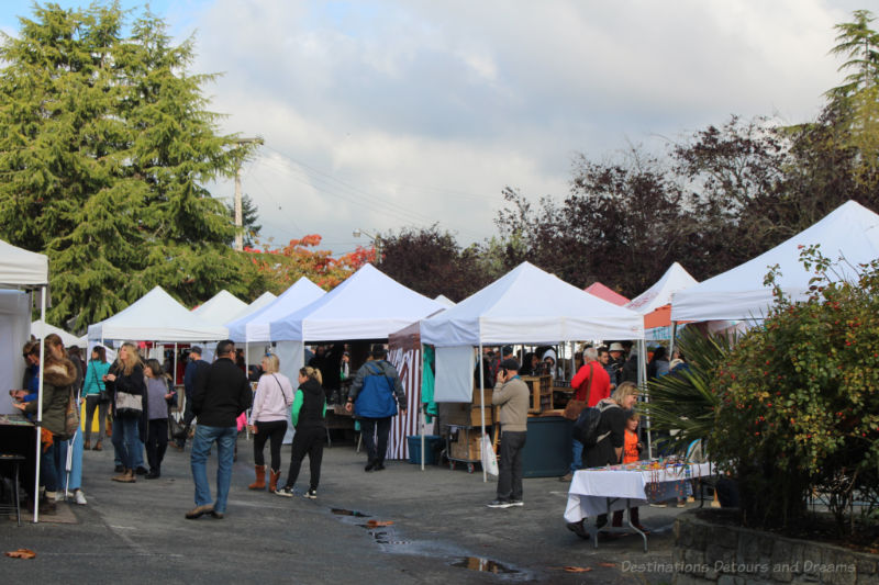 Visitors stroll among booths under tent canopies at the Salt Spring Island Saturday Market