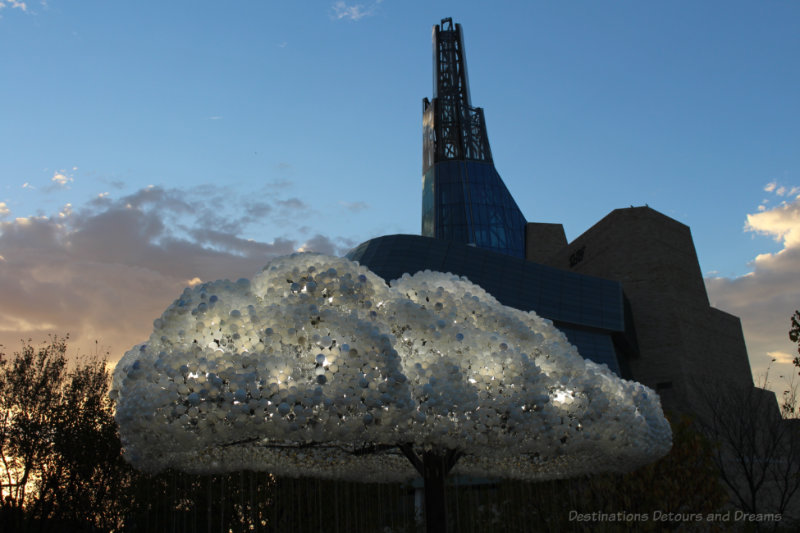 An interactive light art installation looking like a cloud with the Canadian Museum for Human Rights in the background