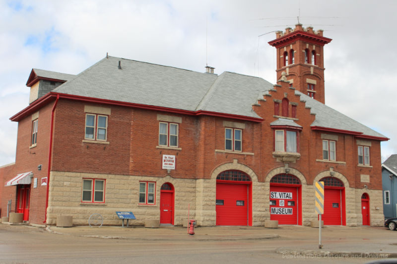 Old brick fire hall with red doors now housing a museum