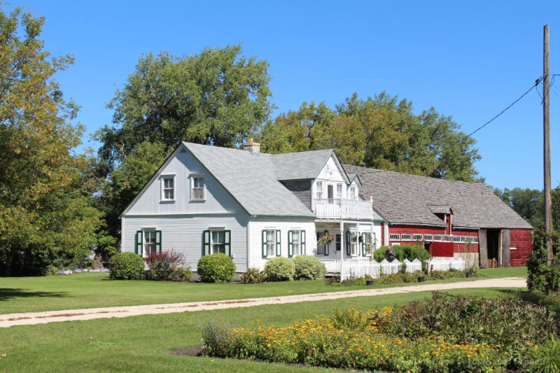 White wooden house and attached red barn in a Manitoba Mennonite street village